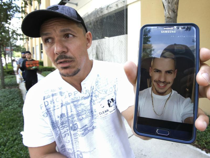 Angel Mendez, standing outside the Orlando Regional Medical Center, holds up a cell phone photo trying to get information about his brother Jean C. Mendez that was at the Pulse Nightclub where a shooting involving multiple fatalities occurred. (AP)