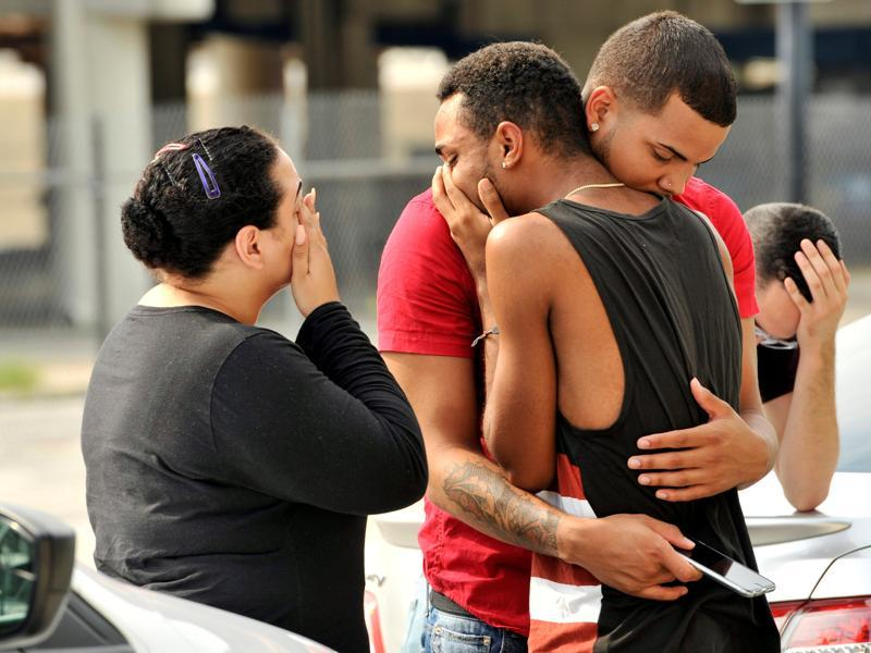 Friends and family members embrace outside the Orlando Police Headquarters during the investigation of a shooting at the Pulse night club. (REUTERS)