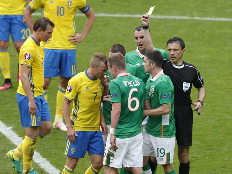 Referee Milorad Mazic, right, shows the yellow card to Republic of Ireland's Glenn Whelan, centre, as he argues with Sweden's Sebastian Larsson, second left. (AP)