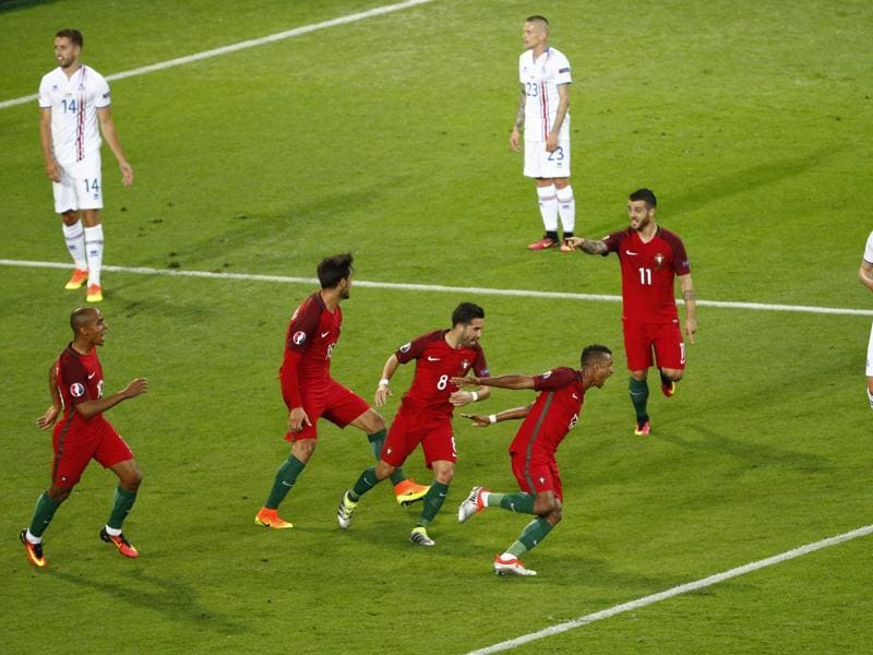 Portugal's players join Nani to celebrate his goal. (REUTERS)