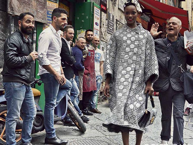 One picture sees the female models walk bashfully though a cheering crowd, but all feature locals going about their daily business, exiting restaurants, selling chocolate and admiring pretty girls. (Dolce & Gabbana)