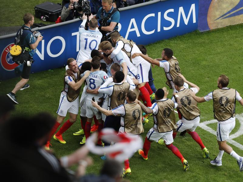 England players rush to the sideline to celebrate the winning goal. (AP)