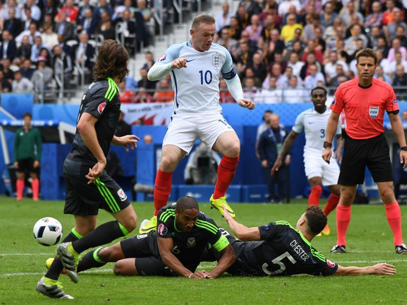England's Wayne Rooney leaps over Wales players. (AP)