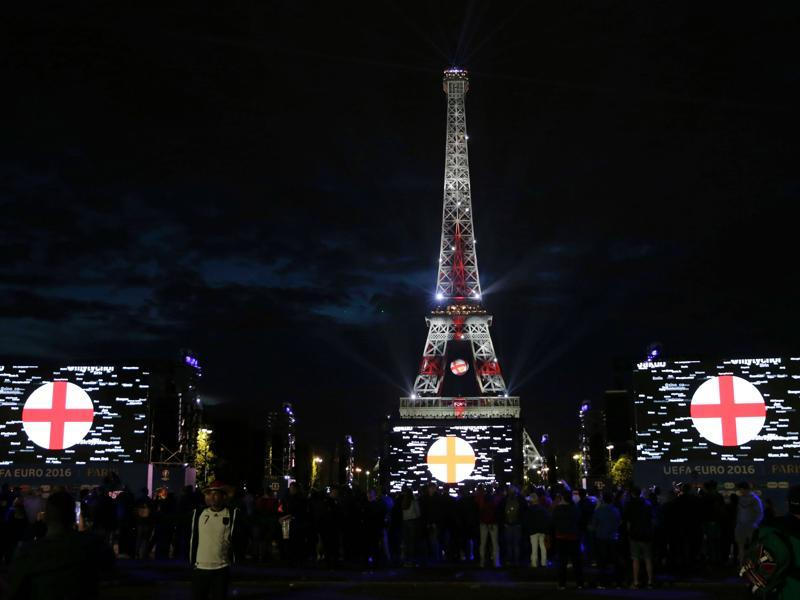 The Eiffel Tower is lit with the colours of England's flag, as seen from the fan zone after the showing of the Euro 2016 group C football match between Germany and Poland. (AFP photo)