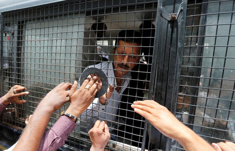 A convict in connection with a riot in Gujarat in 2002 gestures from inside a police vehicle at a court after the sentencing in Ahmedabad.  (REUTERS)
