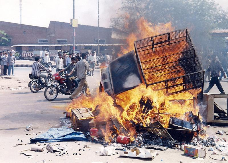 File photo of a biker passing near a burning vehicle during 2002 Gujarat riots.  (PTI)