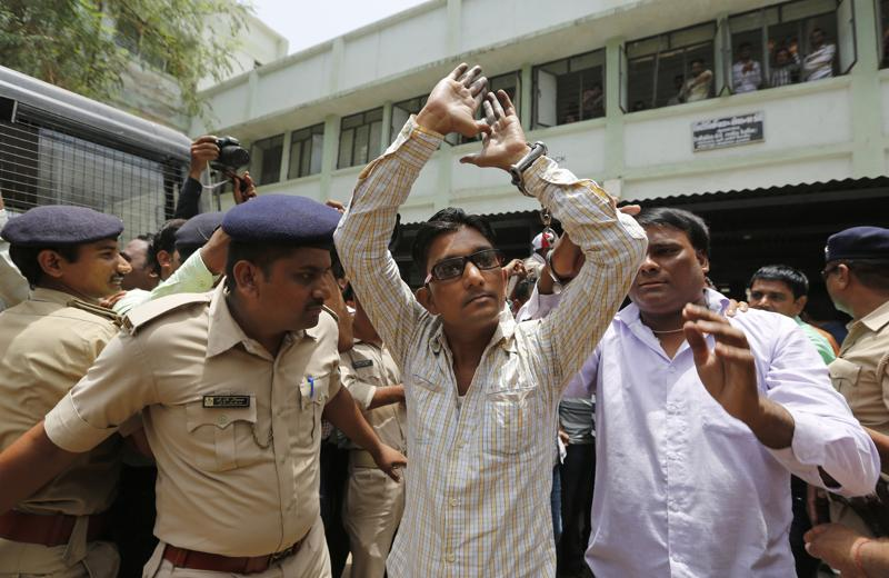 A man convicted for the 2002 Gujarat riots is taken back to jail after the court announced the lengths of the sentences in Ahmadabad. (AP)