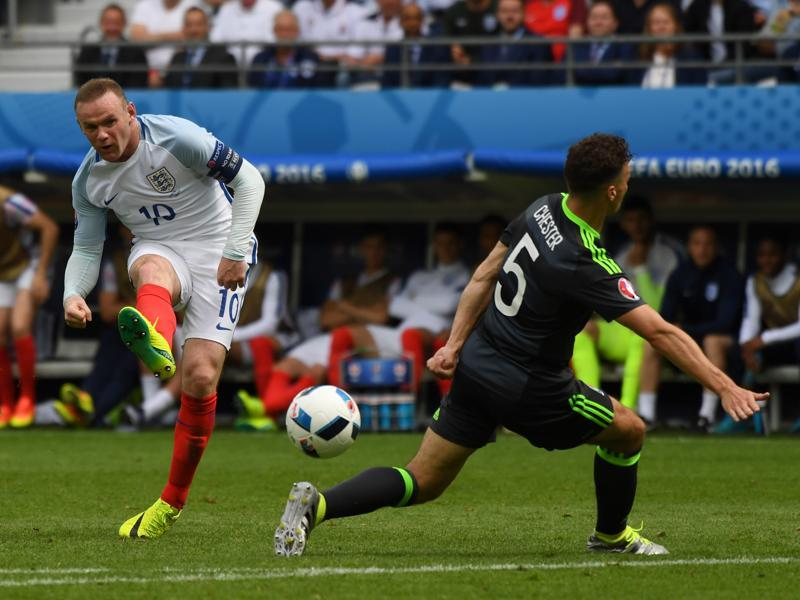 England's Wayne Rooney, left, attempts a shot at goal. (AP)