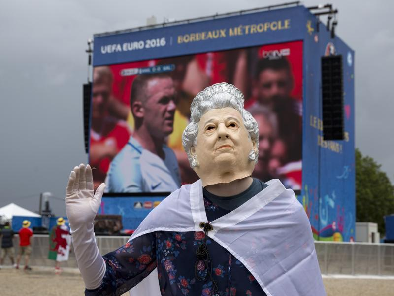 A British fan wearing a mask representing Britain's Queen Elizabeth II waves to other fans. (AP photo)