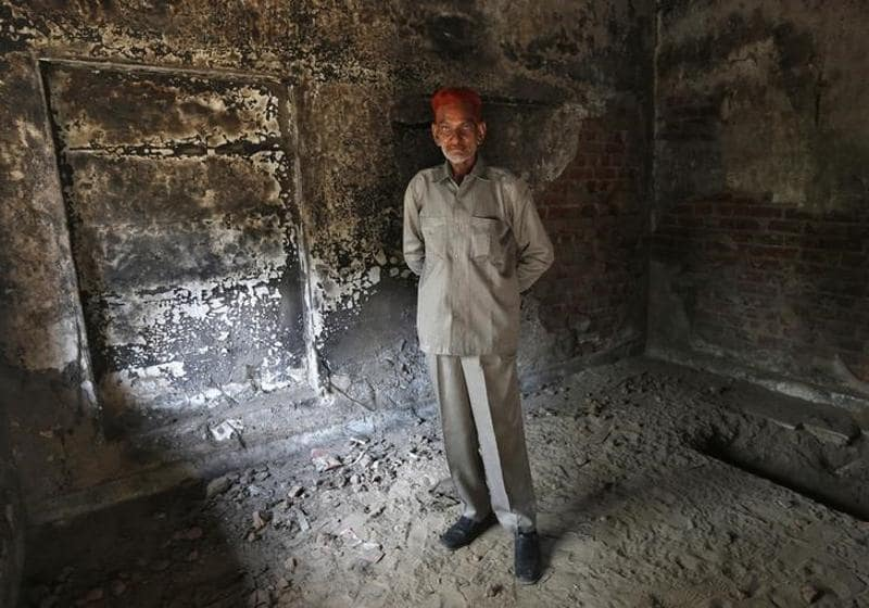 Sayeed Khan Pathan poses inside his house which was burnt and damaged in the Gujarat 2002 riots at the Gulbarg Society. (reuters)