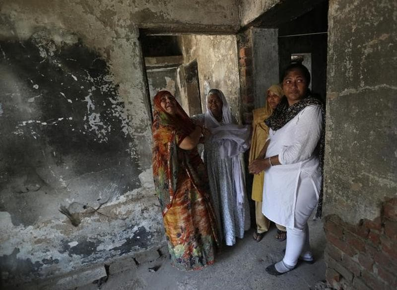 Survivors of the 2002 Gujarat riots weep inside a house that was burnt and damaged in the riots at the Gulbarg Society, (reuters)