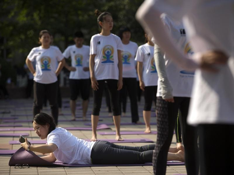 A participant checks her cellphone at the start of a group yoga session at a park in Beijing. (AP)
