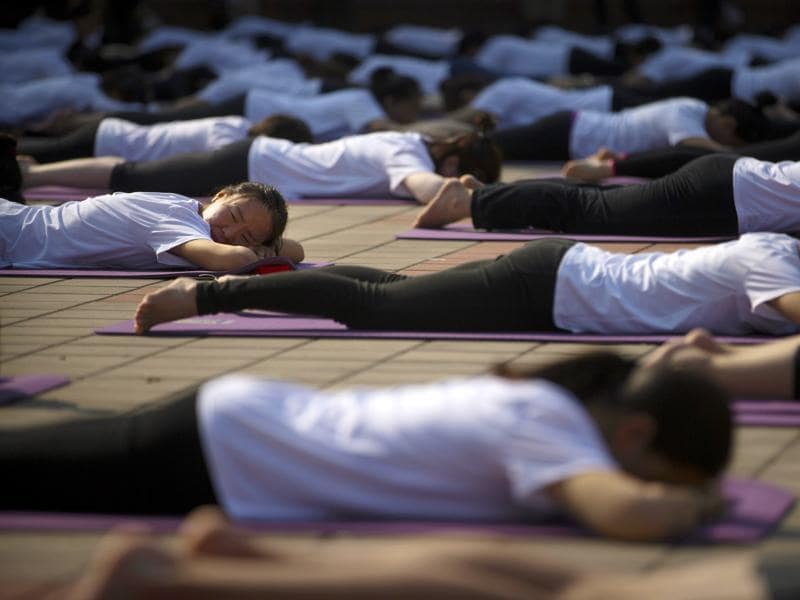 Participants stretch out during a group yoga session at a park in Beijing, Saturday, June 18, 2016.  (AP)