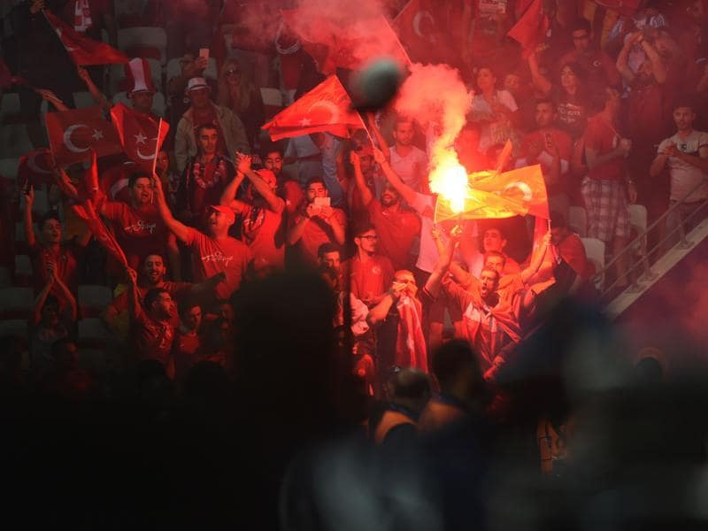 Turkey supporters carry a flare following their teams defeat during the Euro 2016 group D match. (AFP photo)
