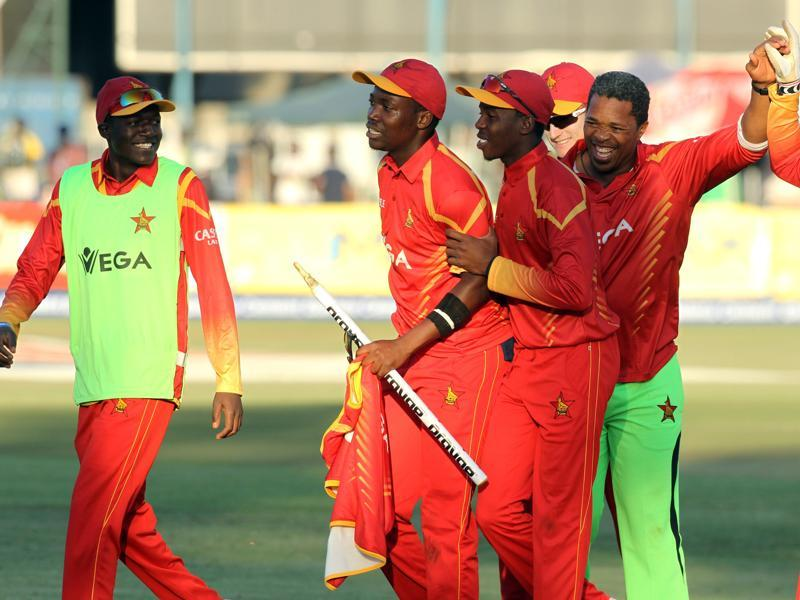 Zimbabwean players and their coach, Makhaya Ntini, second right, celebrate their win. (AP)