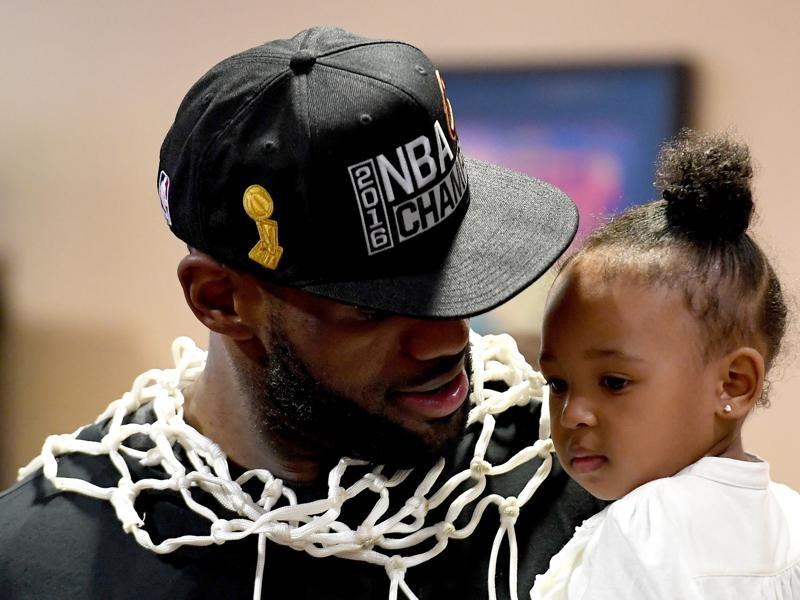 LeBron James holds his daughter Zhuri during a press conference after the game. (AFP)