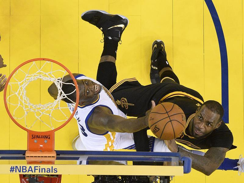 LeBron James, right, shoots against Golden State forward Draymond Green. (AP)