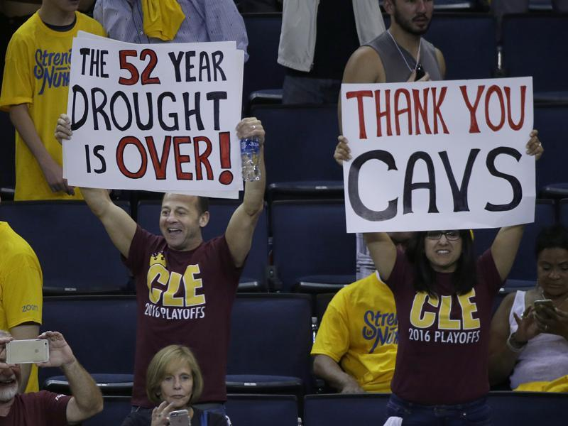 Cleveland Cavaliers fans hold up signs alluding to the fact that the win broke Cleveland's 52-year wait for a major sports title. (AP)