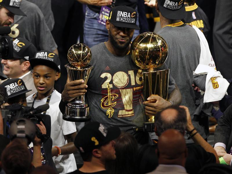 LeBron James (23) celebrates with the Larry O'Brien championship and Bill Russell MVP trophies. (Reuters)