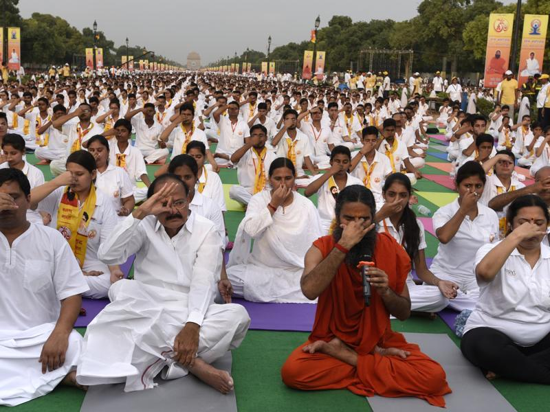Union minister Venkaiah Naidu practices yoga with Ramdev and Acharya Balkrishan at Rajpath. (sonu mehta/ht photo)