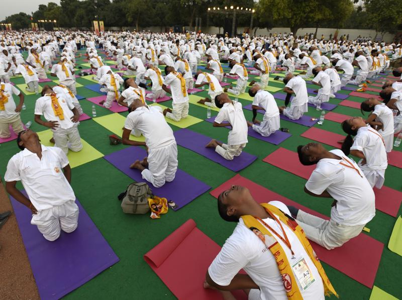 Participants practice a yoga posture during a rehearsal at Rajpath. (Sonu mehta/ht photo)
