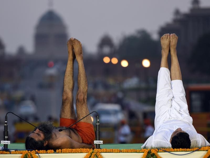 Ramdev and Acharya Balkrishna teach volunteers a yoga pose. (Sonu mehta/HT Photo)