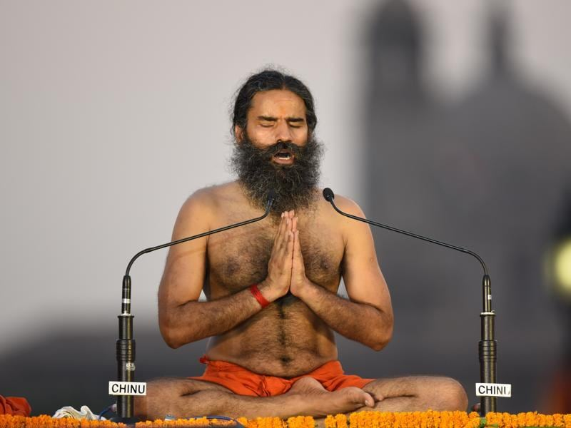 Ramdev teaches a yoga posture to participants. (Virendra singh gosain/ht photo)
