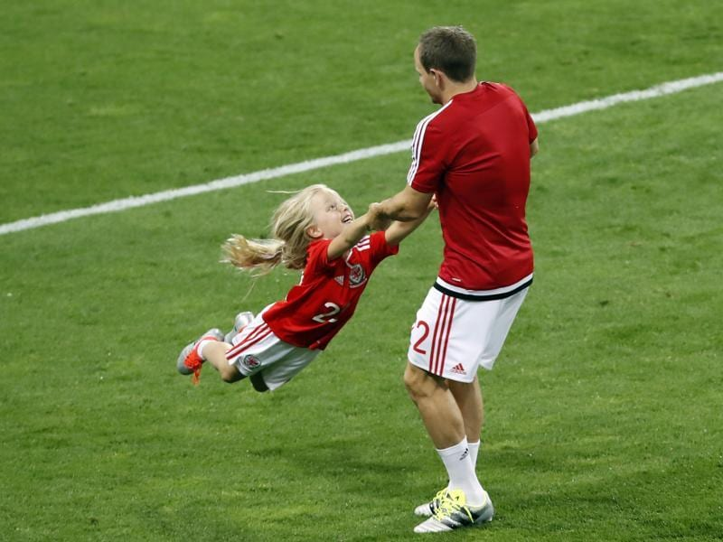 Wales's David Vaughan plays with a child on the pitch after his team defeated Russia 3-0 in a Euro 2016 Group B football match at the Stadium municipal in Toulouse. (AP Photo)