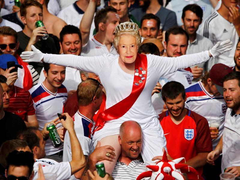 An England fan wears a mask of Queen Elizabeth II as he rides on the shoulders of his mates gathering in Saint Etienne ahead of their team's match against Slovakia. (Reuters Photo)