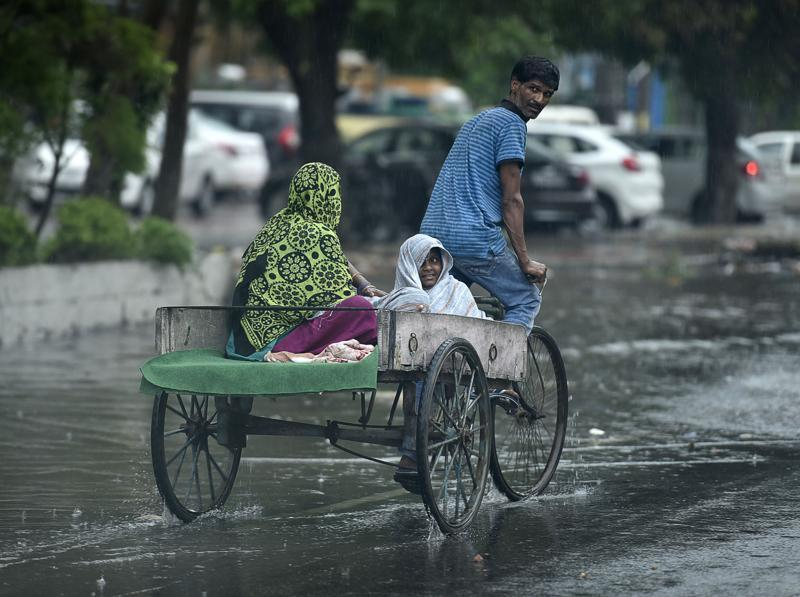 Commuters on a waterlogged road on a rainy day in Amritsar. (Gurpreet Singh/HT)
