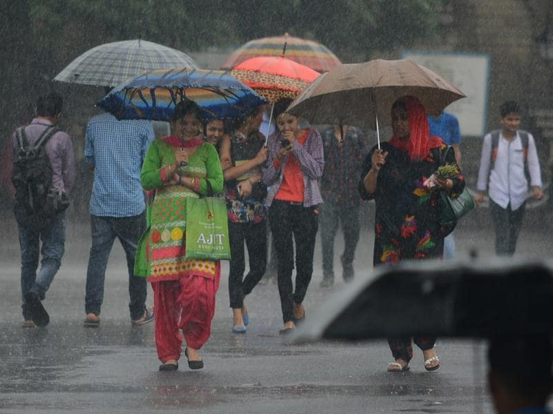 Some hide under umbrellas while others feel the rain at The Ridge in Shimla on Wednesday. (Deepak Sansta/HT)