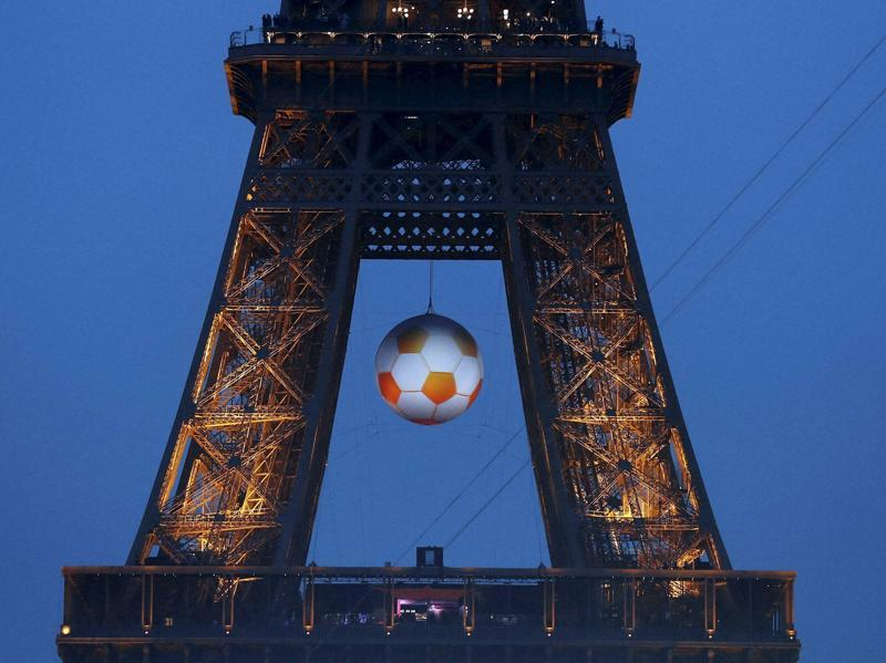 A giant football hangs on the Eiffel Tower during the Euro 2016 Group A match between France and Romania. (AP photo)