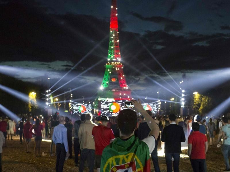 People watch on a giant screen a Euro 2016 football match at the fan zone in front of the Eiffel Tower in Paris. (AFP Photo)