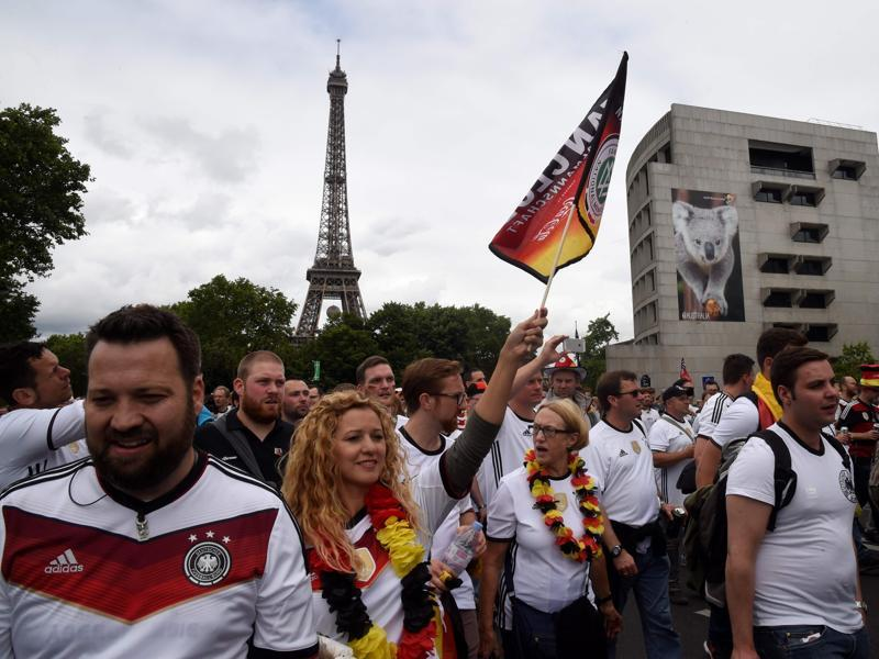 German fans wave national flags and cheer for their team during the fan walk between the Eiffel tower and Parc des Princes, in Paris. (AFP Photo)