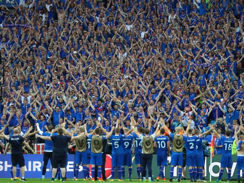 Iceland's players celebrate their victory with their supporters at the end of the match. (AP)