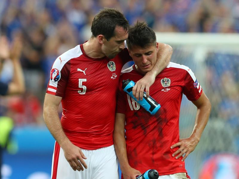 Austria's Christian Fuchs, left, tries to console his teammate, Alessandro Schoepf, at the end of the match. (AP)