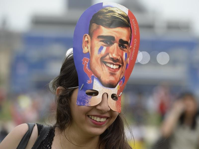 A French supporter smiles with a mask representing Antoine Griezmann inside the fan zone ahead of the first football matches of the Euro 2016 football tournament on June 10, 2016 in Paris.  (AFP PHOTO)