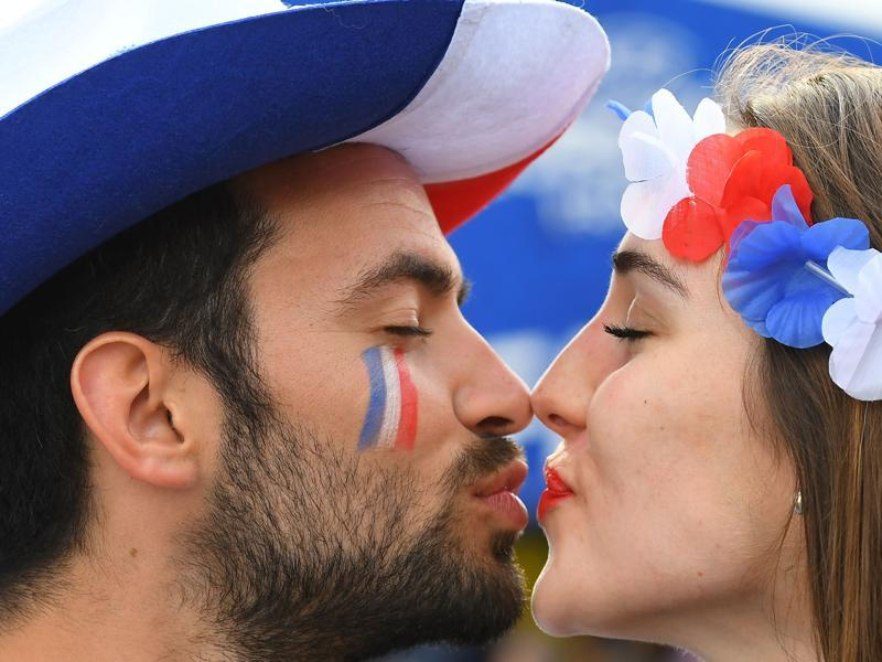 A man and a woman supporting France kiss prior to the Euro 2016 group A football match between France and Romania at Stade de France. (AFP Photo)