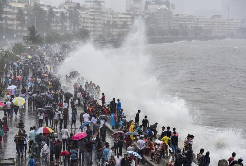 Residents and tourists enjoy a high tide at Marine Drive in Mumbai. People often flock to the tourist hot spot to enjoy the rain.  (Kunal Patil)