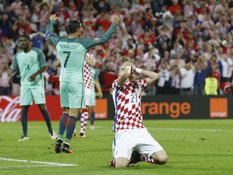 Croatia's Domagoj Vida reacts as Cristiano Ronaldo celebrates Portugal's goal. (Reuters)