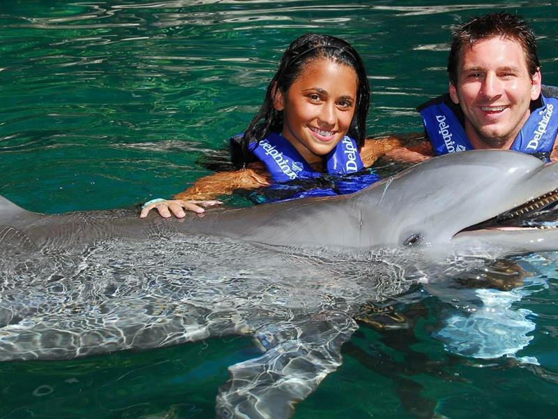 Lionel Messi and girlfriend Antonella Rocuzzo swim with dolphins at the Delphinus aquarium on July 24, 2010 in Playa del Carmen, Mexico. (AP Photo)