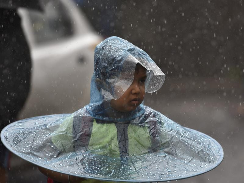 Amid the heavy showers children take all kinds of precautions to deal with the rains.  (Arijit Sen)