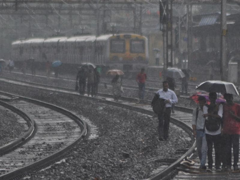 Train passengers often take the tracks to reach their destinations when technical failure brings the city's lifeline to a halt.  (Bhushan Koyande)