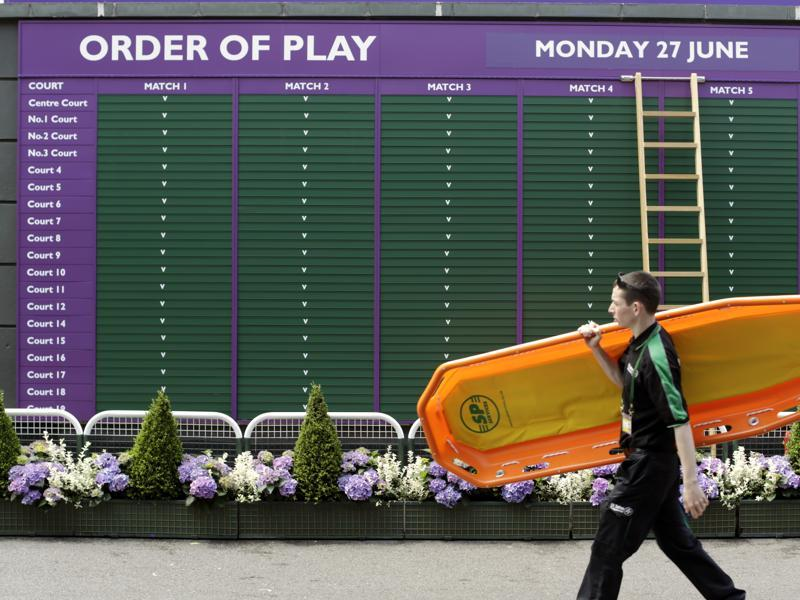 A member of staff walks past the order of play board. (AP)