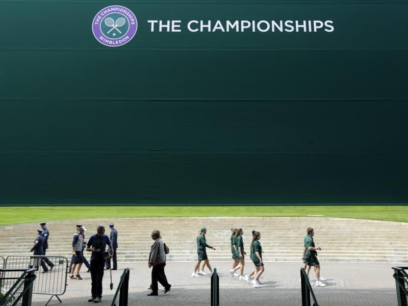 Staff members set up ahead of the start of The Championships. (AP)
