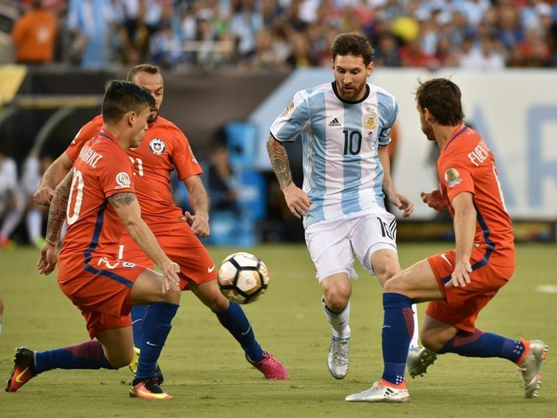 Lionel Messi (#10) steers the ball past three Chilean defenders. (AFP)