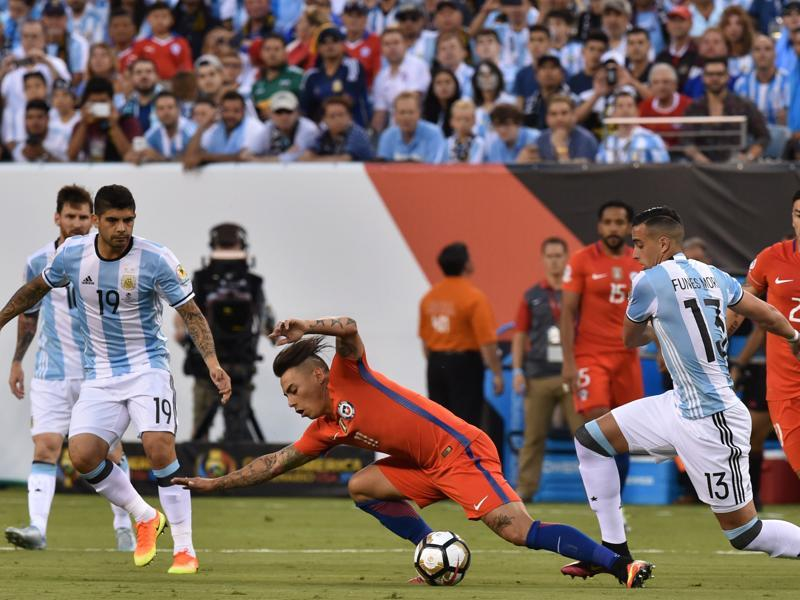 Chile's Eduardo Vargas is fouled by Argentina's Ramiro Funes Mori. (AFP)