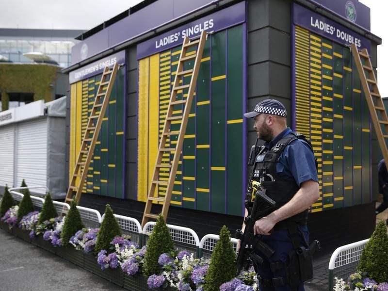 An armed police officer stands guard next to a board displaying the draw. (AFP)