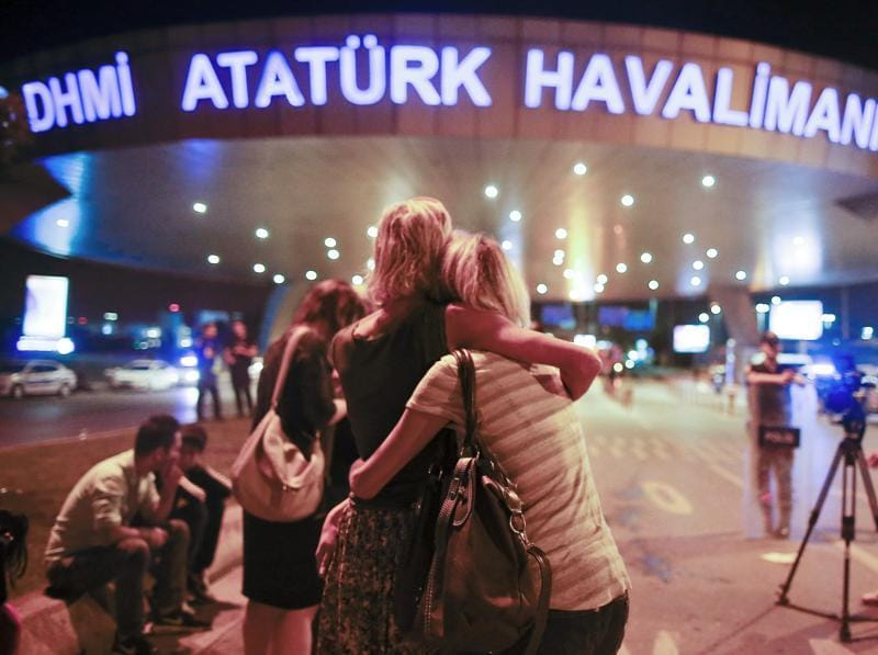 Passengers embrace each other at the entrance to Istanbul's Ataturk airport early on Wednesday following their evacuation after the attacks. (AP)