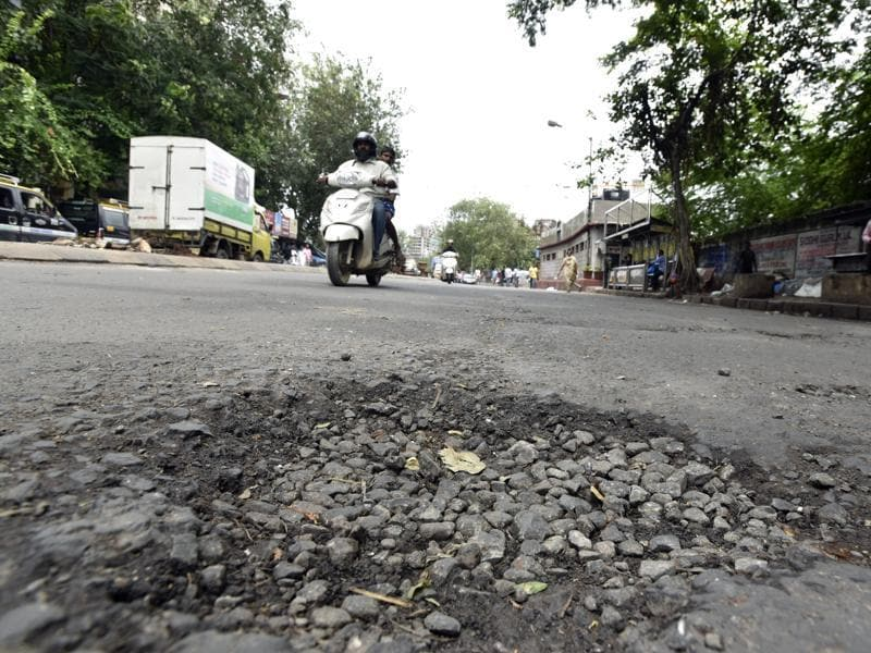 Guru Tegh Bahadur station: This stretch witnesses heavy traffic throughout the day. Such potholes add to the woes of commuters, who brave the rain, traffic and congestion during peak hours, almost everyday.  (Kunal Patil/ Hindustan Times)